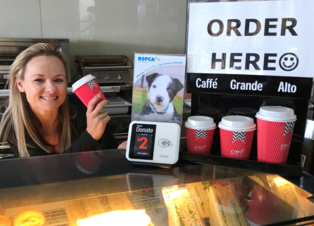 Cafe employee smiles and holds a coffee cup, next to an RSPCA Tap n Give machine on the counter
